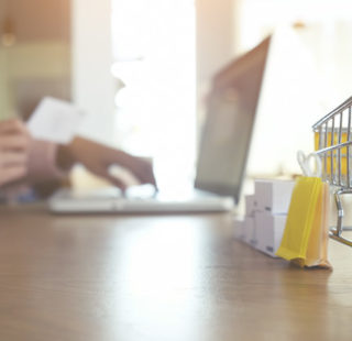Internet online shopping concept with laptop and shopping-cart.Vintage tone retro filter effect,soft focus(selective focus)